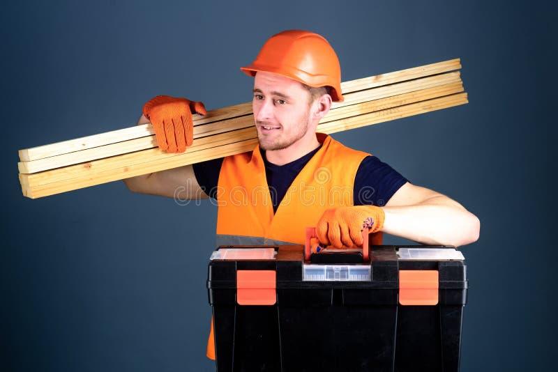 Concepto profesional del carpintero El carpintero, trabajador, constructor, carpintero en cara sonriente lleva haces de madera en fotos de archivo libres de regalías