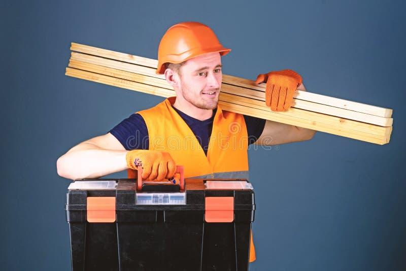 Concepto profesional del carpintero El carpintero, trabajador, constructor, carpintero en cara sonriente lleva haces de madera en fotografía de archivo libre de regalías