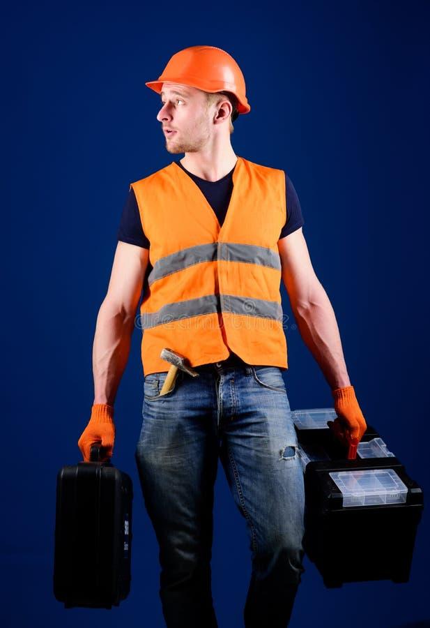 Concepto profesional del reparador El hombre en el casco, casco sostiene la caja de herramientas y la maleta con las herramientas imágenes de archivo libres de regalías