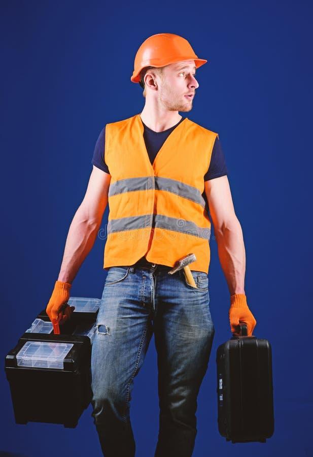 Concepto profesional del reparador El hombre en el casco, casco sostiene la caja de herramientas y la maleta con las herramientas foto de archivo libre de regalías