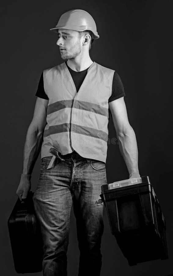 Concepto profesional del reparador El trabajador, manitas, reparador, constructor en cara tranquila lleva bolsos con las herramie imágenes de archivo libres de regalías