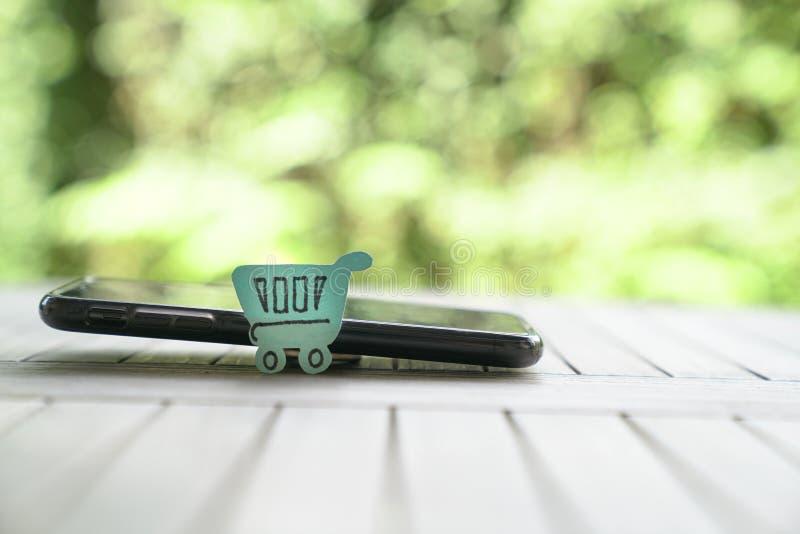 Concepto que hace compras en línea: un carro de la compra de papel en un teléfono móvil imagen de archivo