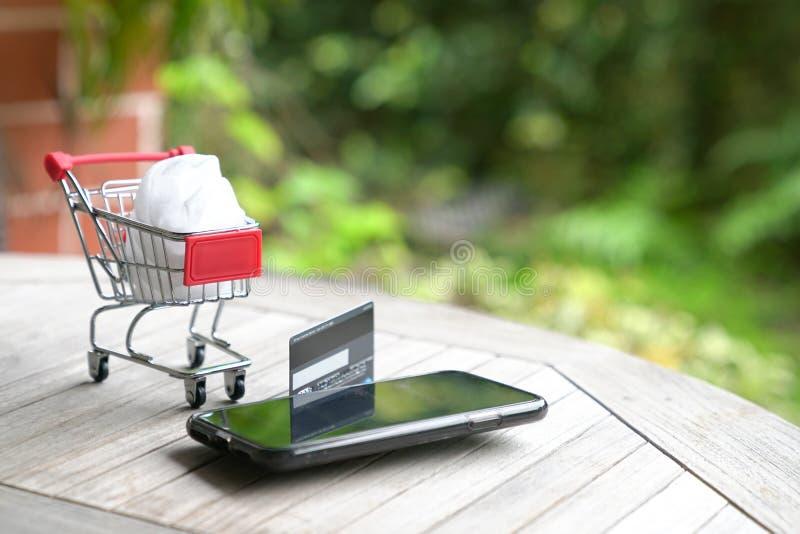 Concepto que hace compras en l?nea: carro de la carretilla y un tel?fono elegante fotografía de archivo libre de regalías