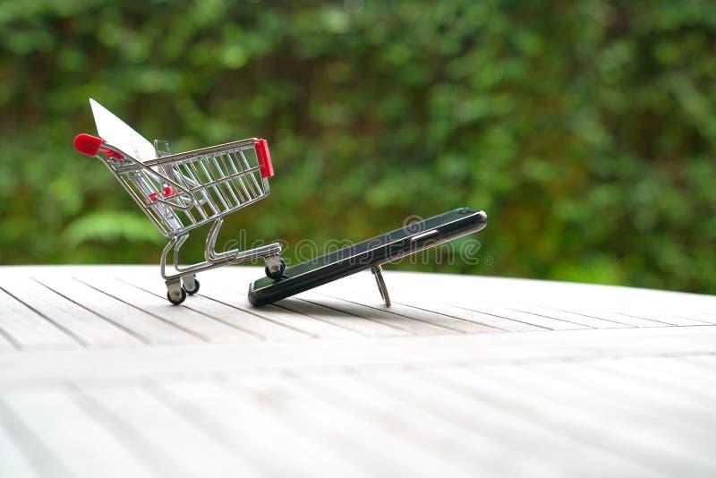 Concepto que hace compras en l?nea: carro de la carretilla y un tel?fono elegante fotos de archivo libres de regalías
