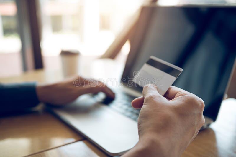 Concepto que hace compras en l?nea con la mano del hombre usando el ordenador port?til y la mirada de la tarjeta de cr?dito para  imágenes de archivo libres de regalías