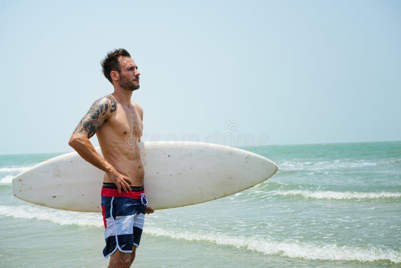 Concepto que practica surf de las vacaciones de las vacaciones de verano de la playa del hombre imagenes de archivo