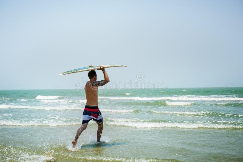 Concepto que practica surf de las vacaciones de las vacaciones de verano de la playa del hombre foto de archivo