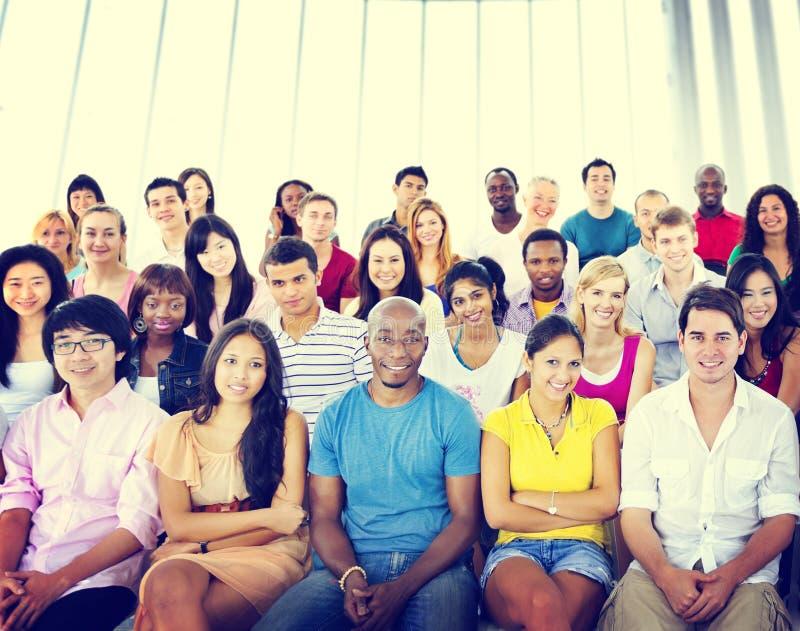 Concepto que se sienta multicolor casual de la audiencia de la muchedumbre de la gente del grupo imágenes de archivo libres de regalías