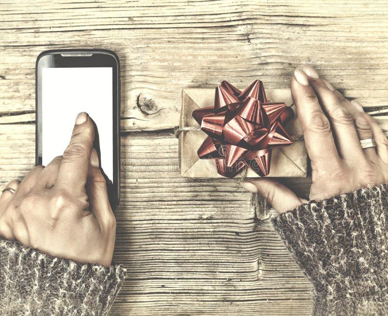 Concepto: Regalos de la Navidad Una persona envía o pide un regalo de la Navidad usando un smartphone Entrega de Internet imagenes de archivo