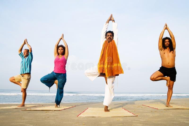 Concepto relajante del grupo de playa de la clase de la yoga fotos de archivo