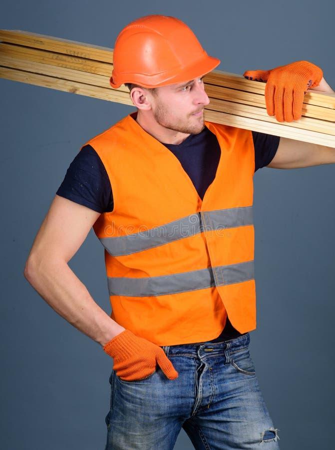 Concepto resistente del trabajador El carpintero, carpintero, trabajador, constructor en cara ocupada lleva haces de madera en ho imágenes de archivo libres de regalías