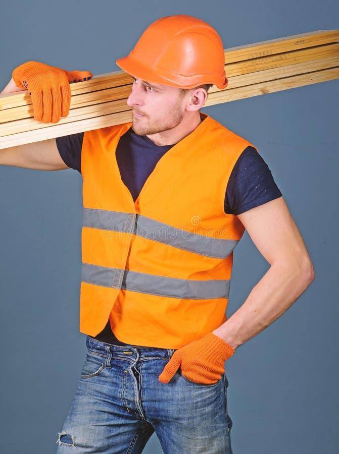 Concepto resistente del trabajador El carpintero, carpintero, trabajador, constructor en cara ocupada lleva haces de madera en ho fotografía de archivo libre de regalías
