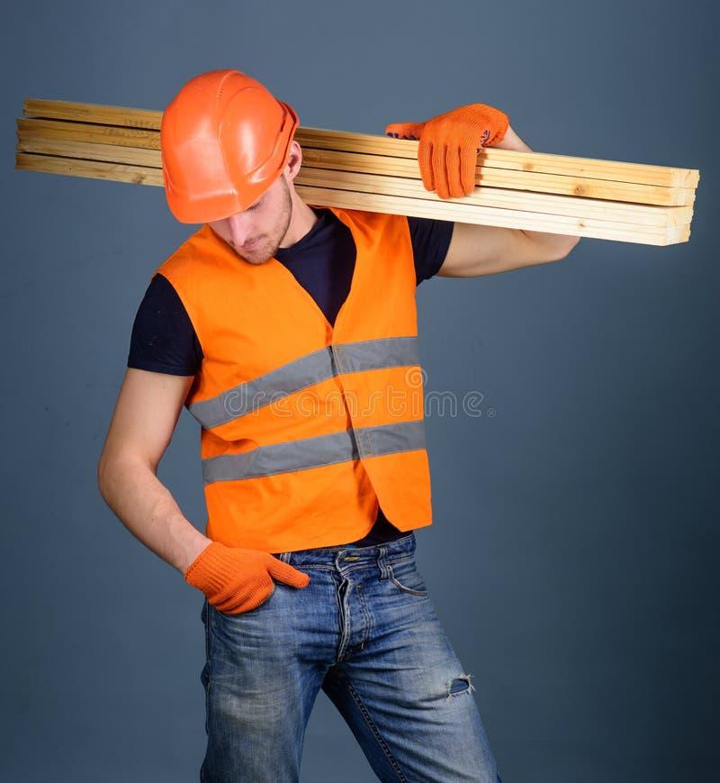 Concepto resistente del trabajador El hombre en casco, casco y guantes protectores lleva a cabo el haz de madera, fondo gris carp imágenes de archivo libres de regalías
