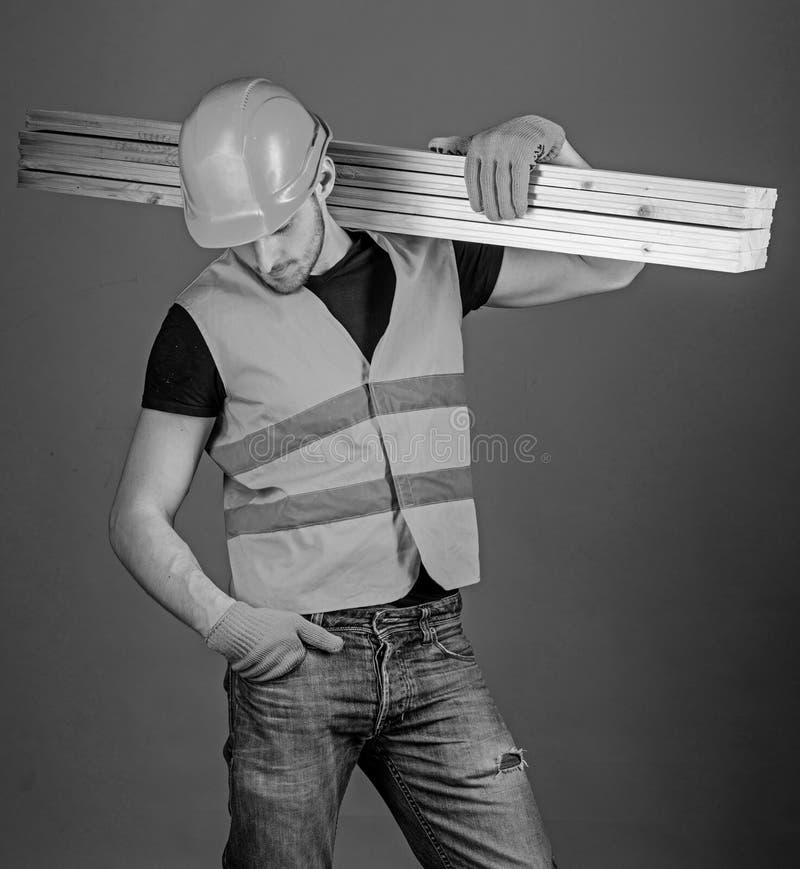 Concepto resistente del trabajador El hombre en casco, casco y guantes protectores lleva a cabo el haz de madera, fondo gris carp imagen de archivo