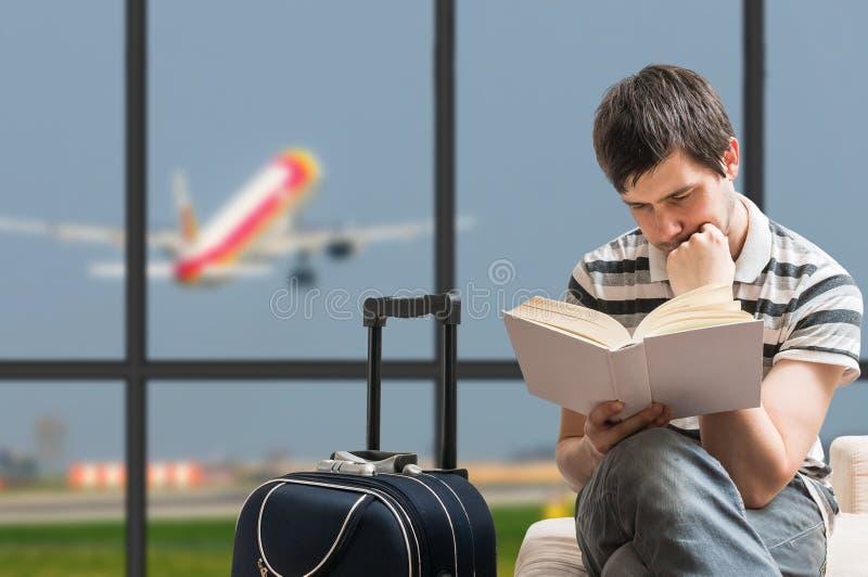 Concepto retrasado del avión El hombre se está sentando con equipaje en aeropuerto fotografía de archivo