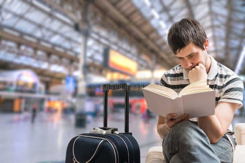 Concepto retrasado del tren El hombre se está sentando en la estación de tren y el libro de lectura foto de archivo libre de regalías