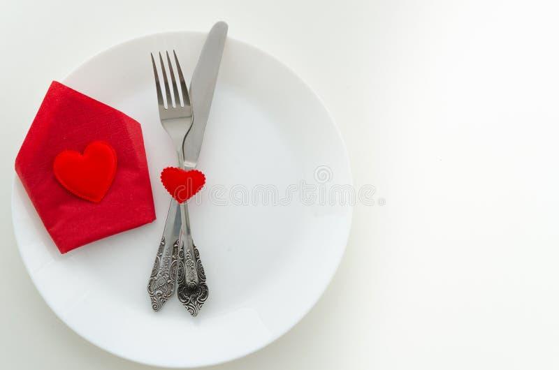Concepto romántico de la oferta de la cena de la visión superior Plato con los cubiertos y la caja de regalo roja con el corazón  imagen de archivo libre de regalías