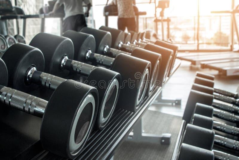 Concepto sano de la aptitud de la forma de vida con filas de pesas de gimnasia y en el gimnasio y un instructor personal para el  foto de archivo