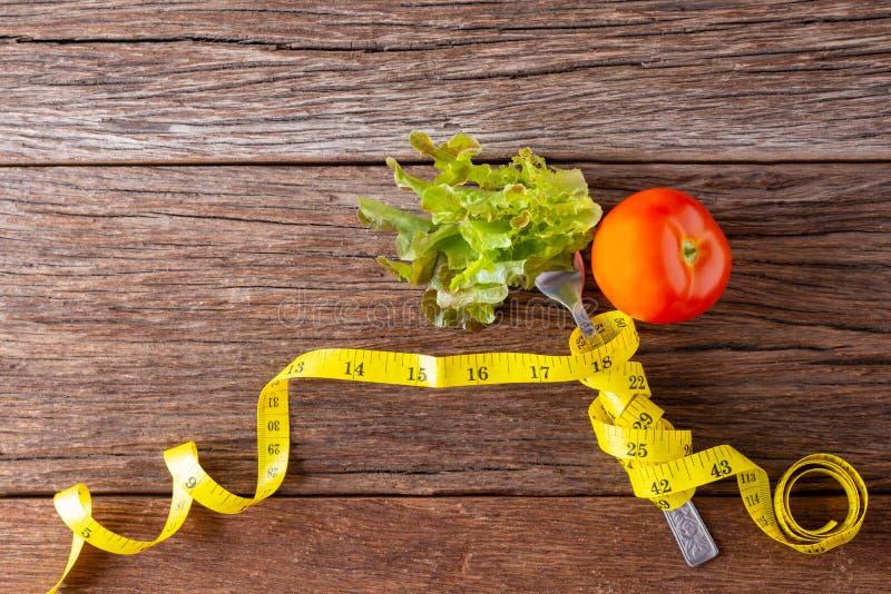 Concepto sano de la consumición Bifurcación y verdura con la cinta de la medida y el tomate fresco en el escritorio de madera Esp imagen de archivo