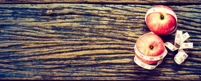 Concepto sano de la dieta manzana roja con la cinta métrica en vagos de madera imagen de archivo