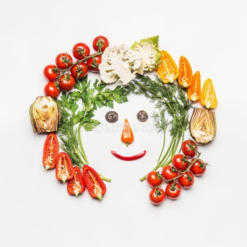 Concepto sano de la forma de vida Cara divertida hecha con los diversos ingredientes de las verduras en el fondo blanco foto de archivo libre de regalías