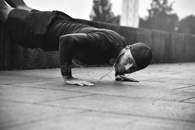 Concepto sano de la forma de vida El ejercicio muscular del atleta empuja para arriba afuera hacia adentro parque de la ciudad imagen de archivo libre de regalías