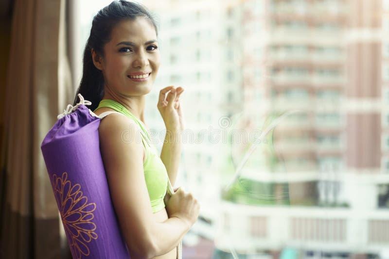 Concepto sano de la forma de vida Mujer que sostiene la estera de la yoga y stan jovenes imagen de archivo libre de regalías