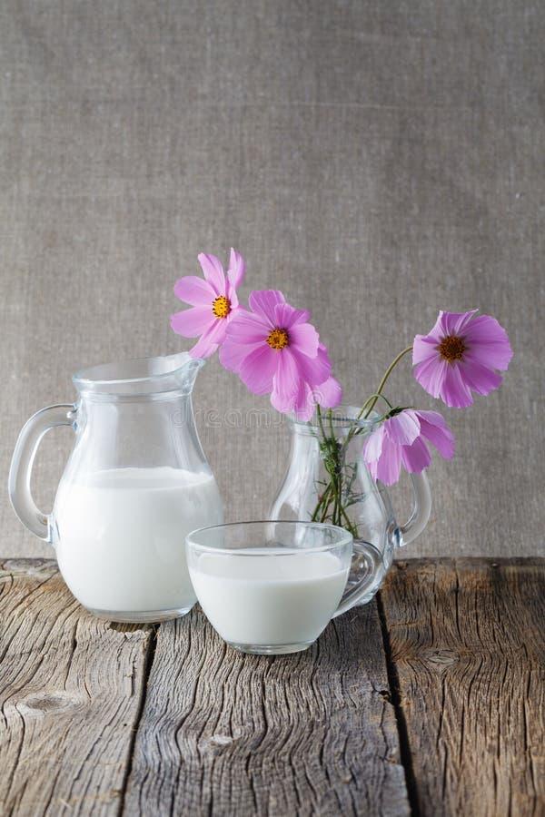 Concepto sano del alimento Taza de leche en la tabla de madera con las flores fotos de archivo libres de regalías