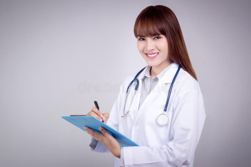 Concepto sano: Escritura asiática joven del doctor en el tablero para la carta paciente foto de archivo