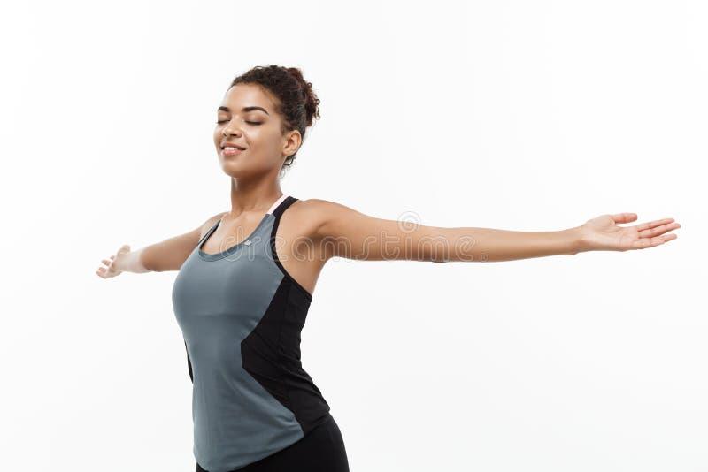 Concepto sano y de la aptitud - el retrato del afroamericano hermoso joven con sus manos extendidas y el closing observa fotografía de archivo