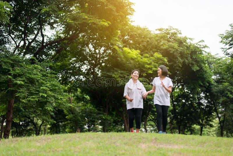 Concepto sano y de la toma del cuidado, retrato de la mujer asiática mayor con la hija que corre en el parque en madrugada junto fotografía de archivo libre de regalías