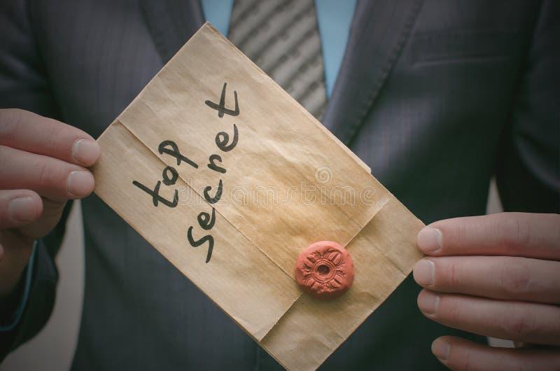 Concepto secretísimo Documentos de alto secreto o mensaje en manos del hombre de negocios imagen de archivo libre de regalías
