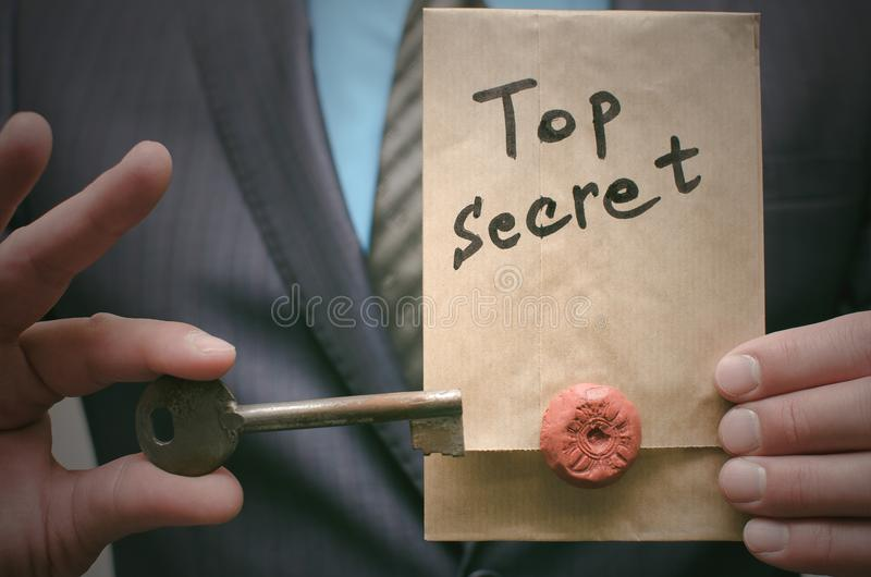 Concepto secretísimo Documentos de alto secreto o mensaje y una llave del desciframiento en manos del hombre de negocios fotos de archivo