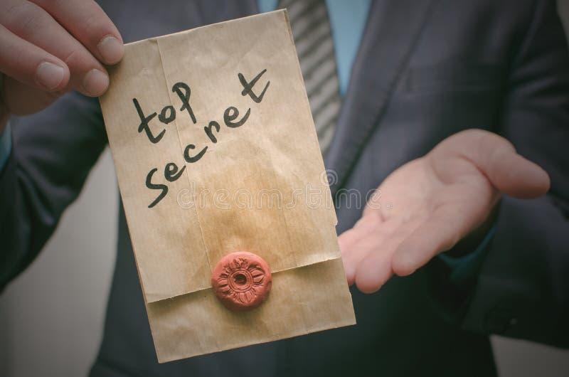 Concepto secretísimo Hombre de negocios que muestra documentos o el mensaje de un máximo secreto en sus manos fotografía de archivo