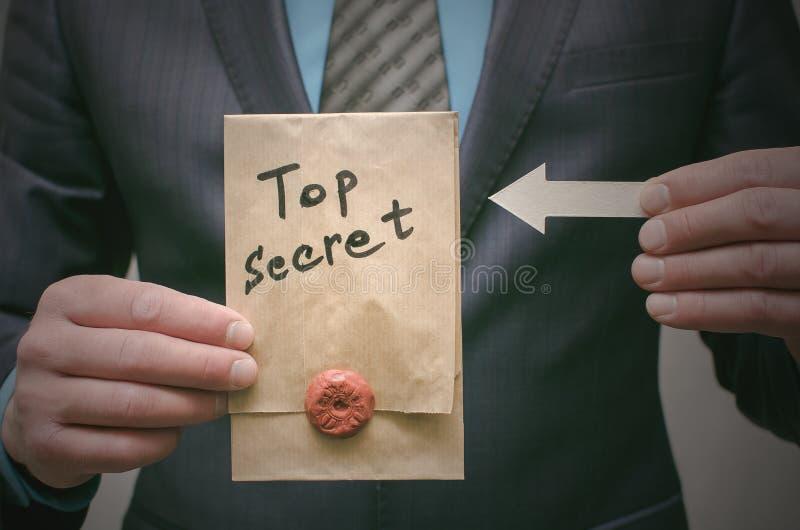 Concepto secretísimo Hombre de negocios que muestra documentos o el mensaje de un máximo secreto en sus manos imagen de archivo libre de regalías