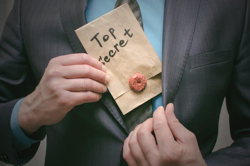 Concepto secretísimo Hombre de negocios que muestra documentos o el mensaje de un máximo secreto en sus manos fotografía de archivo libre de regalías
