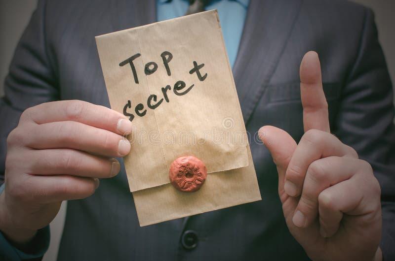 Concepto secretísimo Hombre de negocios que muestra documentos o el mensaje de un máximo secreto en sus manos fotos de archivo libres de regalías