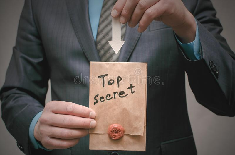 Concepto secretísimo Hombre de negocios que muestra documentos o el mensaje de un máximo secreto en sus manos foto de archivo libre de regalías