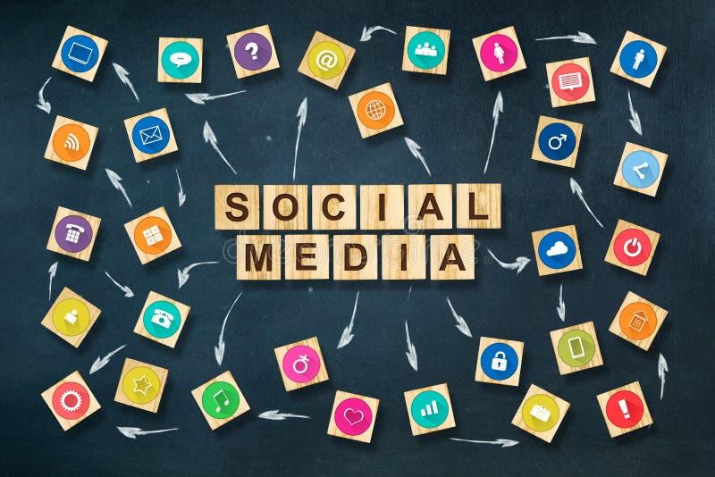 Concepto social de los medios con los iconos sociales en bloques de madera Fondo azul marino C imagen de archivo