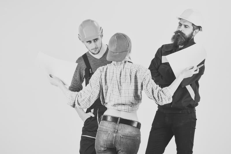 Concepto técnico de la tarea Brigada de trabajadores, de constructores en cascos, de reparadores y de señora que discuten el cont fotos de archivo libres de regalías