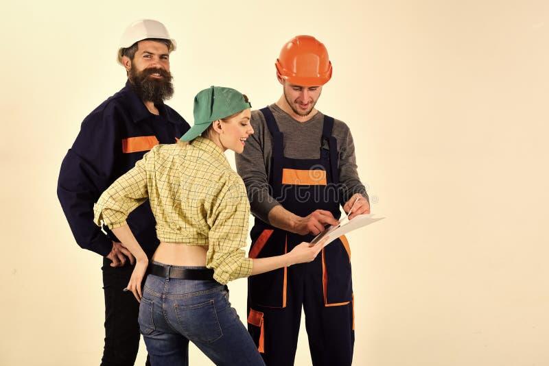 Concepto técnico de la tarea Brigada de trabajadores, de constructores en cascos, de reparadores y de señora que discuten el cont foto de archivo libre de regalías