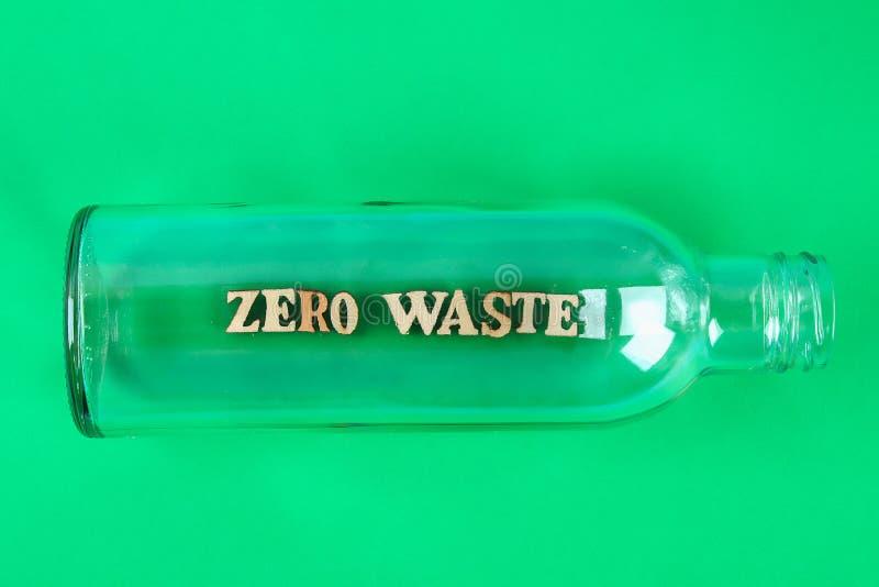 Concepto in?til cero Botella de cristal vacía para las compras y el almacenamiento inútiles cero en fondo verde foto de archivo