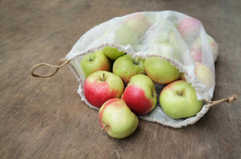 Concepto in?til cero de las compras Manzanas orgánicas frescas en bolso reutilizable de la producción de la malla en la tabla de  imagenes de archivo