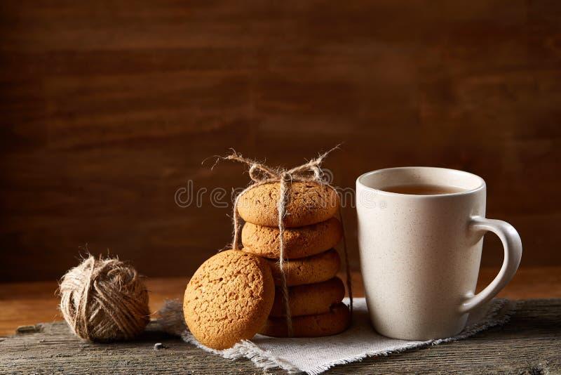 Concepto tradicional del té de la Navidad con una taza de té, de galletas y de decoraciones calientes en una tabla de madera, foc imágenes de archivo libres de regalías