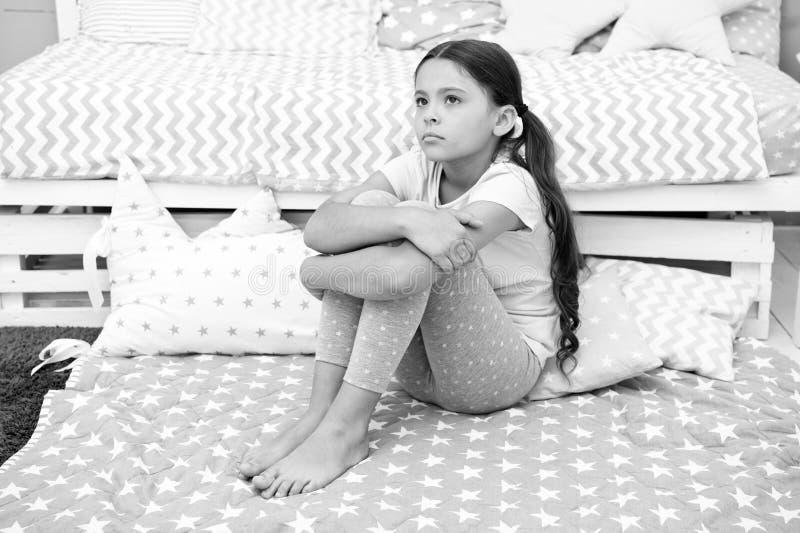 Concepto triste Niña triste El niño triste se sienta en cama Niño triste en dormitorio en casa Quiero jugar foto de archivo libre de regalías