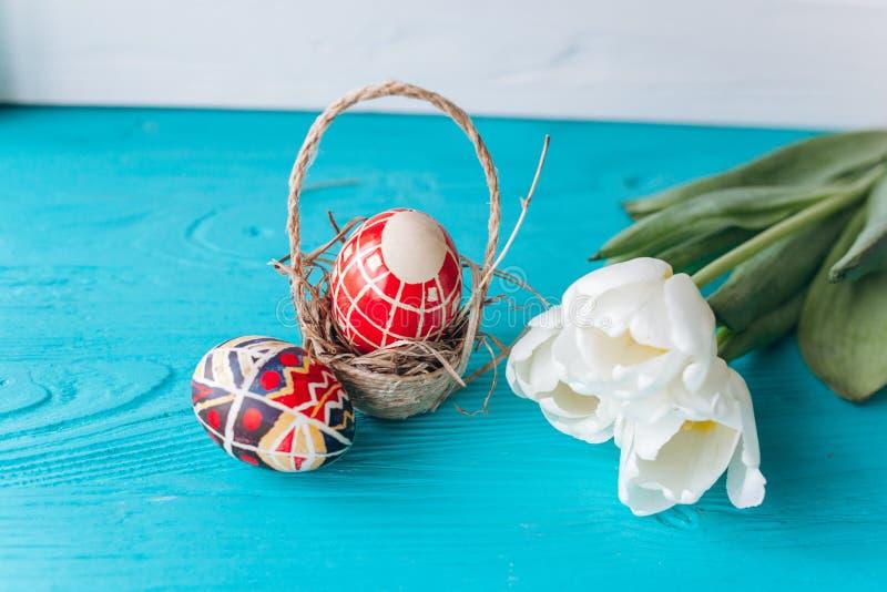 Concepto, tulipanes y huevos de Pascua en un fondo de madera fotos de archivo