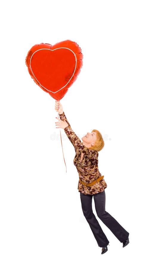 Concepto - una muchacha está volando en un corazón fotos de archivo
