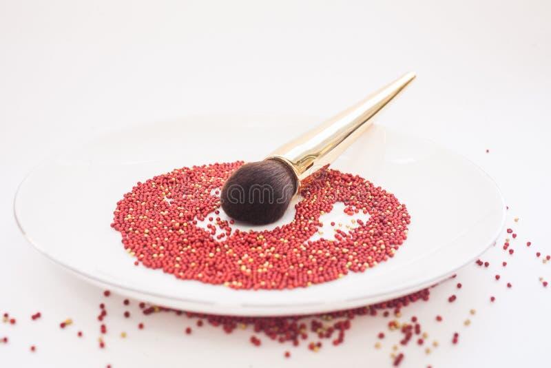 Concepto y arte de la belleza Un cepillo para el polvo con una manija del oro miente en una placa blanca en una preparación roja  foto de archivo libre de regalías