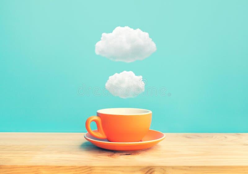 Conceptos de la creatividad de la inspiración con una taza de café en la tabla de madera de la barra con un poco de nube en fondo imagen de archivo libre de regalías