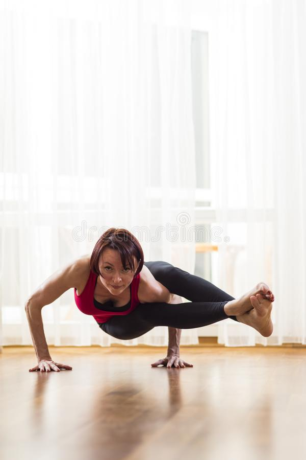Conceptos de la yoga Ejercicio practicante de la yoga de la mujer caucásica dentro en la tarde brillante El sentarse en la actitu imagen de archivo libre de regalías